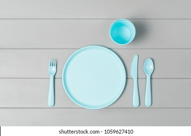 Set of empty, pastel plastic tableware bowls, spoons, knifes and forks isolated on gray wooden background. Flat lay, top view with minimal style.