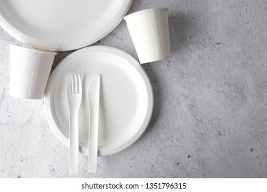 set of empty reusable disposable eco-friendly plates, cups, utensils on light white and grey concrete table top with copy space. Top view.