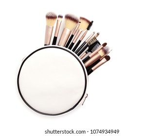 Set of essential professional make-up brushes and cosmetic bag isolated on white background