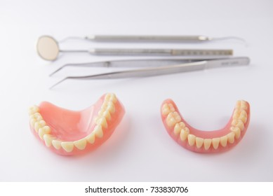 Set of false teeth and dental tools on white background
