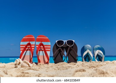 b24aaf70dc61b0 Set of family sandals on the sandy beach with blue sky as a background