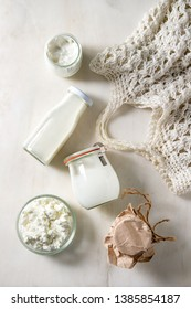 Set of farm dairy produce cottage cheese, milk cream, yogurt in reusable glass jars and bottle with knitted bag over white marble background. Eco friendly shopping. Flat lay, space