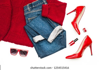 Set of fashion clothes on a white background. Red sweater, jeans, red patent leather shoes and sunglasses. Stylish lady. Flat lay