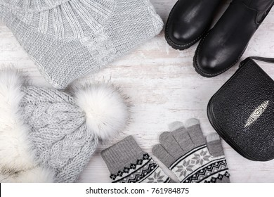A set of fashionable winter women's clothing. Wool sweater, shoes, handbag, fur hat and gloves on white wooden background.
