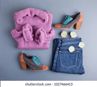 Set of female stylish clothes on grey background. Women`s winter or autumn stylish outfit. Flat lay, top view.
