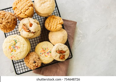 Set of festive cookies on a wire rack. Peanut butter, pecan, oatmeal, shortbread, snickerdoodle round biscuits. Top view. White stone background with copy space.
