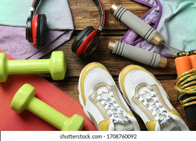 Set of fitness equipment and accessories on wooden background, flat lay