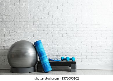 Set of fitness inventory on floor near brick wall. Space for text