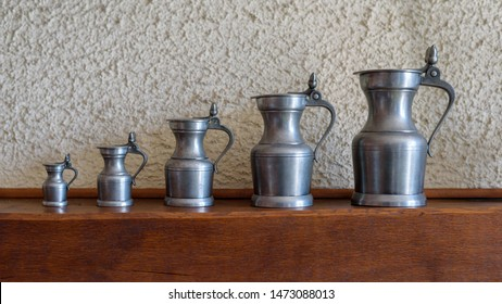 Set of five antique pewter jugs of different sizes.