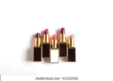 Set of five different colors open lipsticks in row. Isolated on white top view make up set. Lip glosses collection.