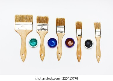 Set of five new brushes different size with color paint tests on white background