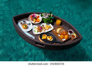 Set of floating breakfast tray in swimming pool with fried egg omelette ,sausage, ham,bread, fruit, juices, and other.Breakfast in swimming pool, floating breakfast set in tray in resort.