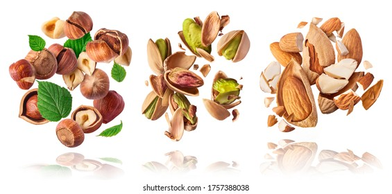 A set with Flying in air fresh raw whole and cracked pistachios, almonds and hazelnut isolated on white background. Concept of Pistachios almonds and hazelnut is torn to pieces close-up.