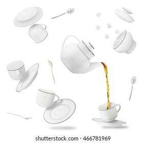 Set of flying and falling tea cups, saucers and pot isolated on white background. Gravity concept