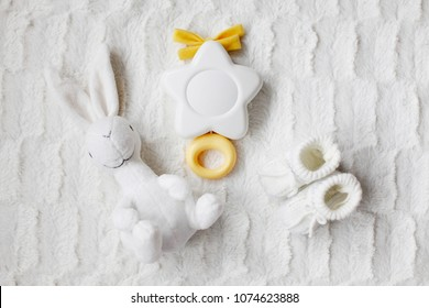 A set of folded white baby clothes with shoes and toys on a white blanket
