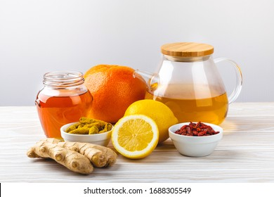 Set of food against flu, cold, viruses. Glass teapot with ginger and lemon tea, honey, grapefruit, turmeric, goji berries, white wooden background. Immunity stimulating natural remedy for good health