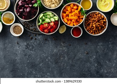 Set food for cooking healthy vegetarian food. Spiced chickpeas, baked pumpkin and beets, quinoa and vegetables on dark stone background with copy space top view