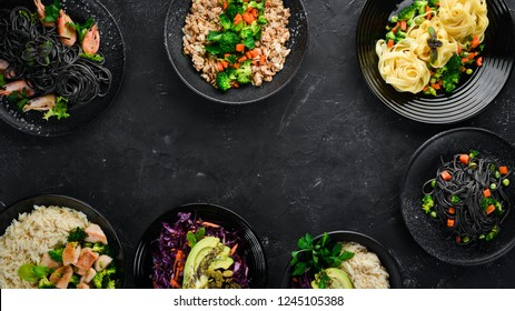 A set of food and dishes. Pasta, rice, risotto, salad. On a black background. Free copy space.