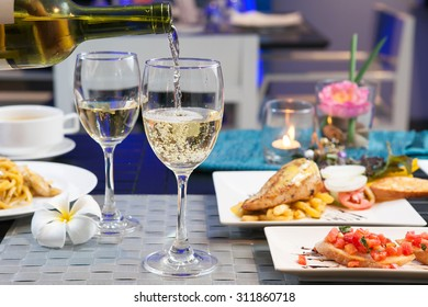 Set of food and Tasting-White wine pour in a glass on foods table