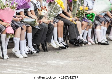 set foots of children of first-graders in school uniforms with flowers at a school event