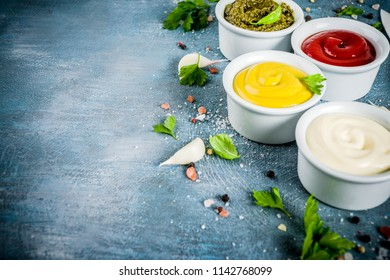 Set of four classic sauces - ketchup, mayonnaise, mustard, pesto - with herbs and spices. Blue concrete background top view copy space
