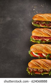 Set of four complete deli sandwiches filled with assorted meat slices and vegetables over dark background with copy space