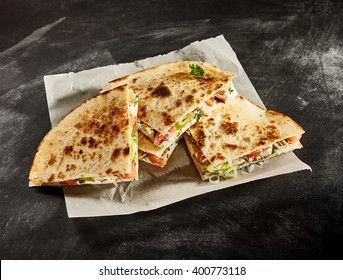 Set of four delicious cooked wheat tortilla quesadillas stuffed with onion, tomato and herbs in wax paper on dark background