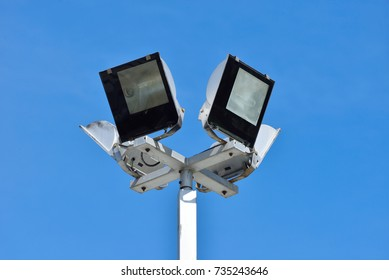 Set of four floodlights mounted on metal post with blue sky background, Lighting pole tower at the sports stadium, car park and ground