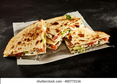 Set of four nutrious cooked chicken wheat tortilla quesadillas stuffed with onion, tomato and herbs in wax paper on dark table