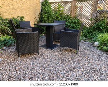 Set of four synthetic rattan chairs with table on gravel in garden with green growth and wooden fence.