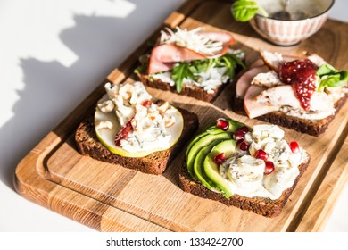 Set of four toasts on wooden board. Cereal bread with: avocado,egg and creamy cheese; pear, gorgonzola, hazelnut;  roasted turkey, apple, cranberry sauce; prosciutto, parmesan, arugula, cream cheese.
