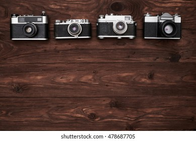 A set of four vintage cameras with a copy space isolated over wooden background