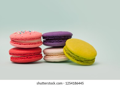 A set of French macaron. French sweets. A lot of colourful cakes on light blue background