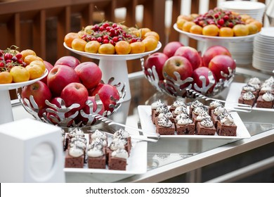 A set of fresh fruit and cakes on a table at an outdoor party