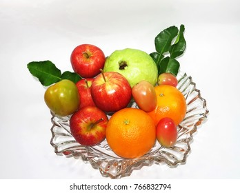 a set of fresh fruits ( apple,orange,guava,tomato) with green leaves are  in the clear glass bowl,beautiful background