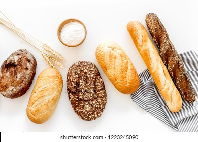 Set of fresh homemade bread. Bread assortment. Loaf, baguette. White and brown bread on tablecloth near ears and bowl with flour on white background top view