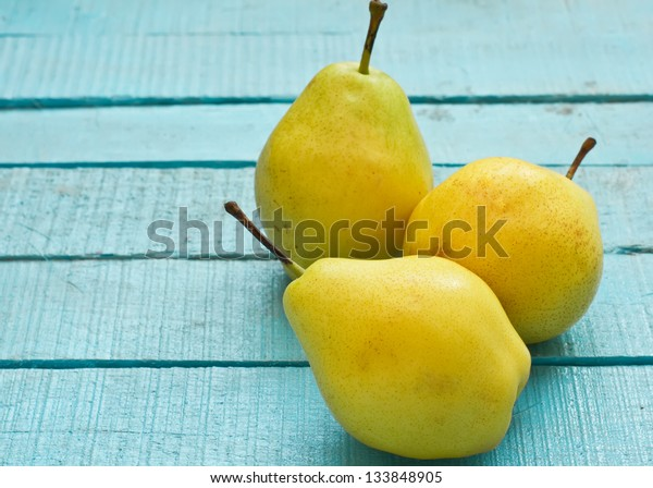 Set of fresh pears on  blue wooden background
