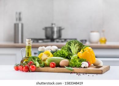 Eine Reihe frischer Rohgemüse Tomate, Ei, Pilze, Salat, Pfeffer, Squash auf einem weißen Holztisch in einem modernen Küchenraum.Gesund essen.Bio-Lebensmittel.