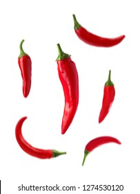 Set with fresh red chili peppers falling against white background