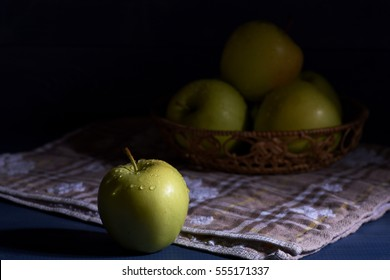 Set of fresh wet green apple with drops near wicker basket with apples on checkered towel or napkin on dark blue vintage wooden background, selective focus