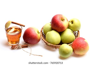 Set of fruit placed in wicker bowl near hot tea glass. Apples and tea with cinnamon sticks isolated on white background. Eco diet and autumn concept. Composition of apples and rustic entourage