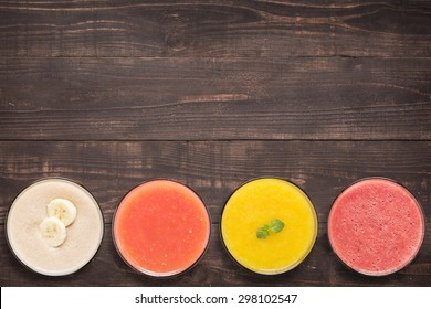 Set of fruit smoothie and juice in glasses on wooden background with a lot of copy space for your text or editing.