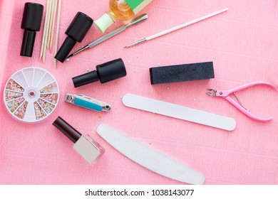 Set for gel manicure procedure, top view. Bottles of nail polishes, wooden sticks, tweezers and file closeup on pink background.