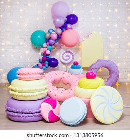 set of giant artificial sweets and pastry decorations over brick wall background