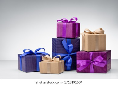 Set of gift boxes on gray background. Crafts from needlework and colored paper, decorated with satin ribbon bows. Happy holidays, copy space.