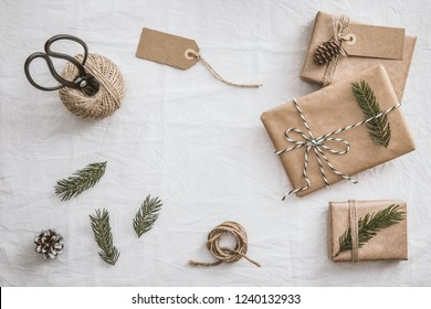 Set for gift wrapping. Presents wrapping inspirations. Gift wrapping. Eco style: natural rough paper, ball of jute, spruce twigs and retro scissors. Copy space