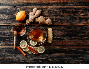 Set of ginger, honey, dry cinnamon, tea and green and lemon on dark wooden background. top view. space for text