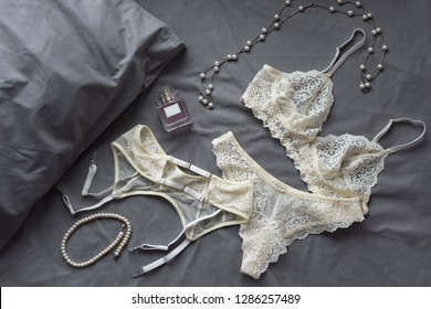 Set of glamorous stylish sexy lace lingerie with woman accessories on grey bedsheets background. Flat lay woman essentials for holiday. Underwear, perfume and necklace. Shopping and fashion concept