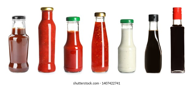 Set of glass bottles with different delicious sauces on white background