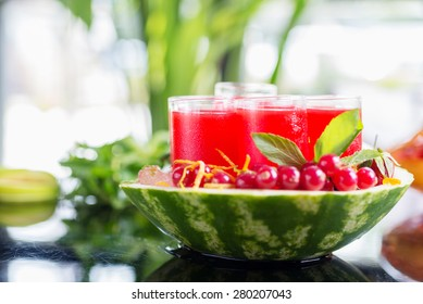 Set of glasses with alcohol cocktail with cranberry juice on a table in a restaurant with a creative composition of ice watermelon and fresh cranberries. soft focus